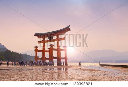 MIYAJIMA, JAPAN - MAY 27: Tourists walk around the famous floating torii gate of the Itsukushima Shrine on Miyajima at sunset on May 27,2016 in Miyajima, Japan