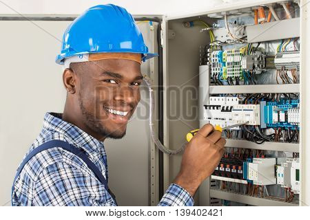 Portrait Of Happy African Male Technician Checking Fusebox With Screwdriver