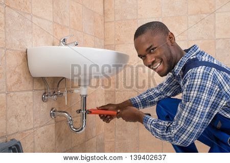 Young African Male Plumber Repairing Sink In Bathroom