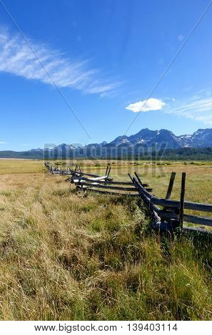 Idaho's Sawtooth mountains provide a scenic background for grassy meadows and rustic, crooked-rail fences.