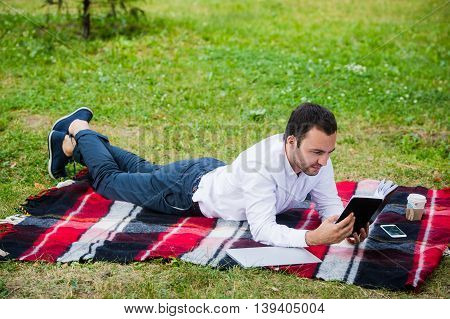 handsome young businessman reading book lying in the park.