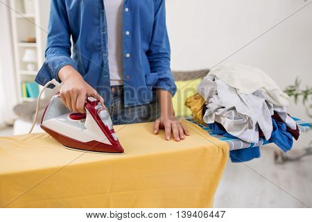 Beautiful youn woman ironing blouse on ironing board