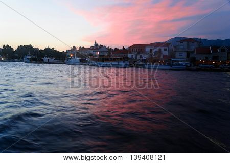 Red sunset over Sucuraj port, Croatia.  SUCURAJ, HVAR ISLAND, CROATIA - JUNE 26, 2016: Red sunset over Sucuraj port on Hvar. The port is an important base for trade and popular touristic destination.