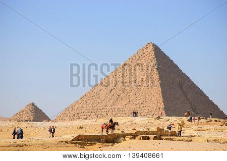Famous Egyptian pyramids in Giza, near Cairo,Egypt GIZA, EGYPT - FEBRUARY 1, 2009: Tourist visiting the most famous Egyptian pyramids in Giza, Egypt. It is the only one of the Seven Wonders of the Ancient World.