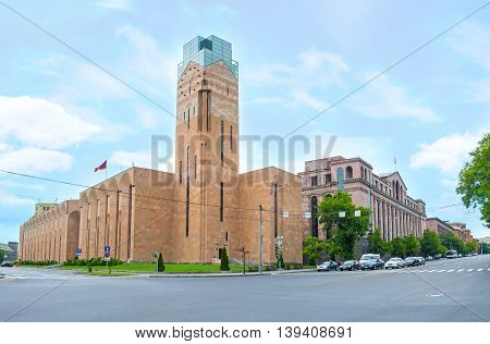 YEREVAN ARMENIA - MAY 29 2016: The modern building of Yerevan City Hall with the high clock tower made of stone and glass on May 29 in Yerevan.