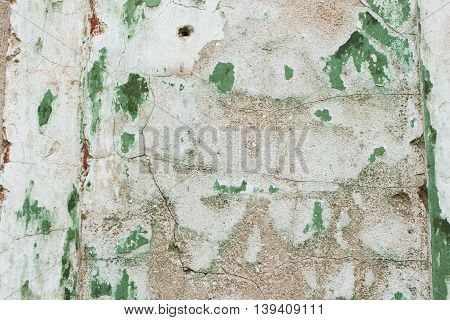 Old crumbling grunge style textured background wall surface . Texture brick wall old abandoned castle with plaster crumble from the time. For background use. Lots of place for writing text around it