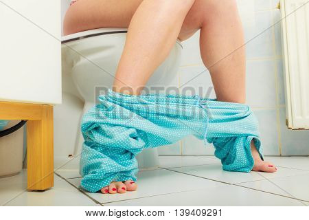 Woman with constipation or diarrhoea sitting on toilet with her blue pajamas down around her legs