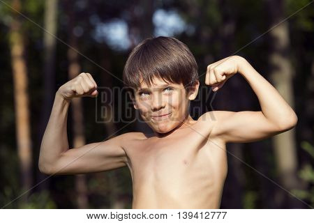 portrait of a boy in nature which shows his muscles