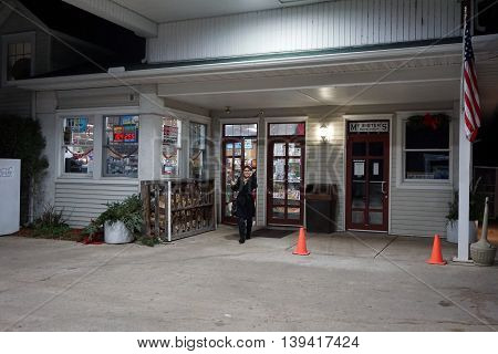 HARBOR SPRINGS, MICHIGAN / UNITED STATES - DECEMBER 25, 2015: A woman walks out of the E-Z Mart convenience store during the night of Christmas in Harbor Springs.