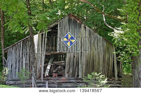 a decorative quilt block on a crumbling old barn