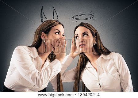 Girl with devil horns speaks to a girl as an angel with a halo