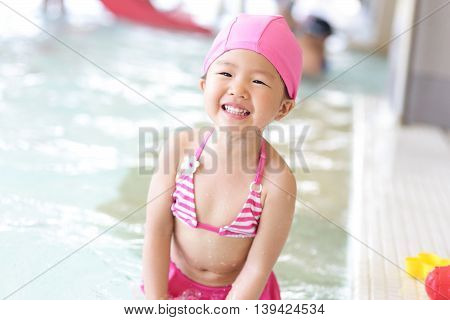 little cute girl wear swimsuit play happily and exciting in the swimming pool asian