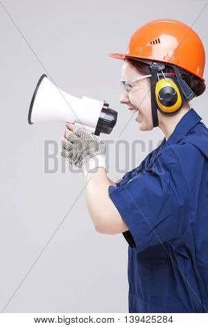 Professions Concepts.Portrait of Expressive Caucasian Female With Loudspeaker Horn Posing In Hardhat Against White. Equipped with Coverall. Vertical Image