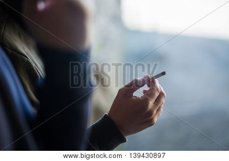smoking, substance abuse, addiction, people and bad habits concept - close up of male hand with cigarette