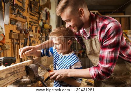 family, carpentry, woodwork and people concept - happy father and little son with rasp grinding wood plank at workshop