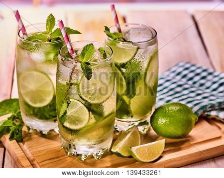 Alcohol straw cocktail. On wooden boards three glasses with alcohol drink and ice cubes. Drink number two hundred twenty nine cocktail mohito and checkered napkin. Country life. Light background.