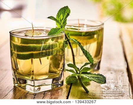 Alcohol drink. On wooden boards are two glasses with alcohol green transparent drink. Drink two hundred twenty three mojito cocktail with lime and mint leaf . Country life. Wooden boards background.