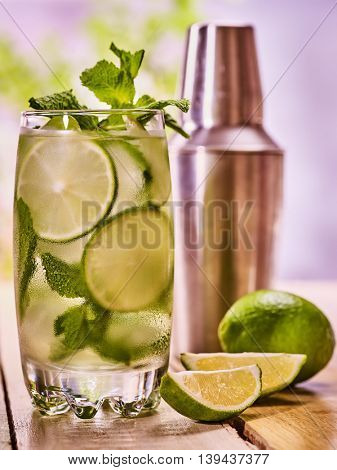 Alcohol lime cocktail. On wooden boards glass with alcohol cocktail and ice cubes. Drink two hundred twenty six cocktail mohito with cocktail shaker and mint leaf. Country life. Light background.