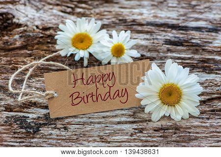 Daisy flowers with a tag Happy Birthday on wooden background