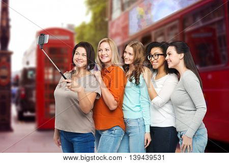 friendship, technology, travel, tourism and people concept - group of happy different women taking picture with smartphone on selfie stick over london city street background