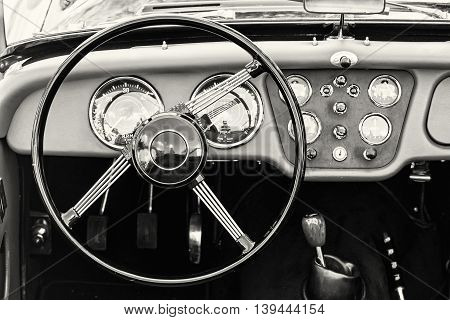 Steering wheel and dashboard in historic vintage car. Black and white photo. Retro automobile interior scene. Driving theme. Old vehicle.