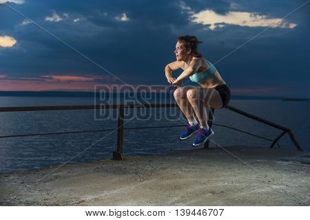 Young caucasian woman in sportswear doing plyometric exercises on pier. Fitness workout outdoors