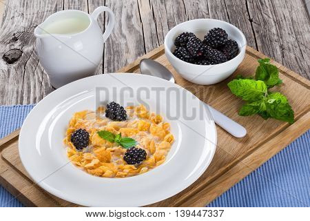 corn flakes with dewberry and milk in white wide rim plate on cutting board with spoon close-up view from above
