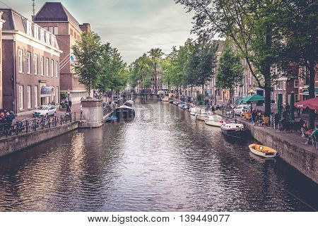 Amsterdam Netherland - June 15 2016: view of a canal in Amsterdam the netherlands. quiet urban scene of the city center with people relaxing on the sides of the channel on a day in early summer
