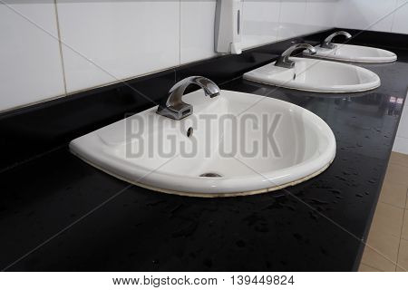 Liquid soap box and white tile sinks in public toilet room.