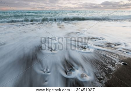 Pebbles on the beach on a black sand and flowing sea water creating nice textures. Long exposure image.