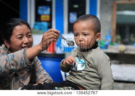 Khumbu Region, Nepal - Oct 20, 2012: Nepali woman feeding her son their house yard on a cold autumn season
