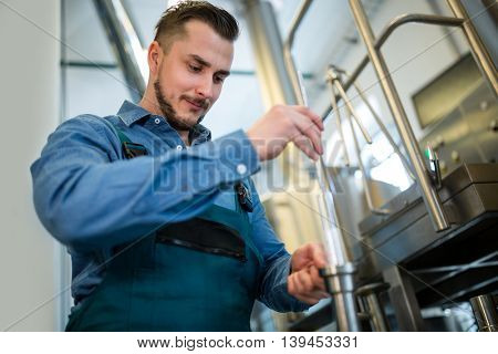 Attentive brewer checking beer with hydrometer at brewery
