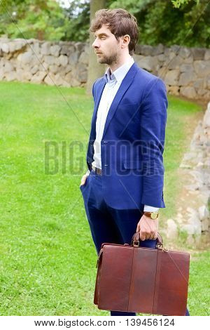 Cool handsome business man with suit in park waiting