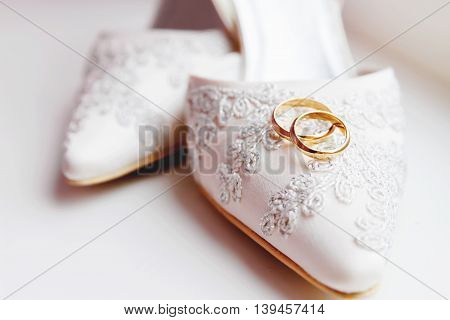 Golden wedding rings on lace silk fabric shoes. Wedding jewelry details. Symbol of love and marriage.