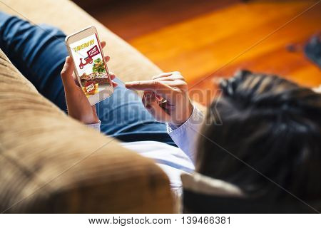 Woman ordering food by internet with a mobile phone while sitting at home.