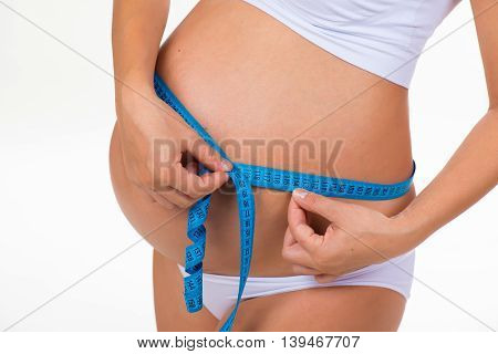 Pregnancy. Health of pregnant women. Measuring size tummy with meter tape