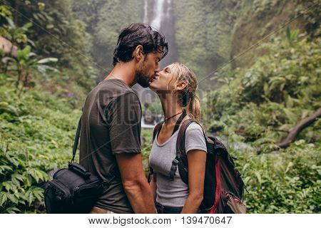 Couple In Love Kissing Near A Waterfall In Forest