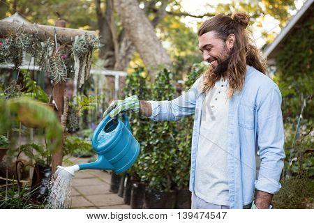 Happy young male gardener watering plants at community garden