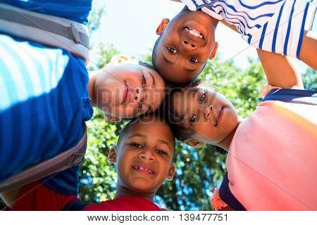 Portrait of happy children forming huddle at park