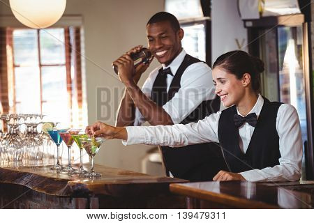 Smiling female bartender garnishing cocktail with olive on bar counter