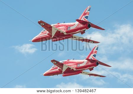 FARNBOROUGH, UK - JULY 17: Low-level flypast by the Red Arrows aerobatic display team at an aviation event at Farnborough, UK on July 17, 2016