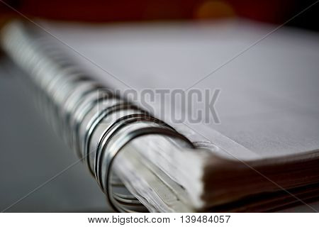 Macro detail of a metal binding spiral of the white notepad on the silver surface