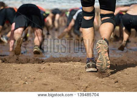 Mud race runners.Crawling, passing under a barbed wire obstacles during extreme obstacle race