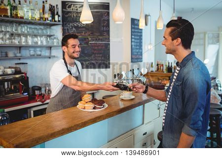 Happy young customer paying through credit card at coffee shop