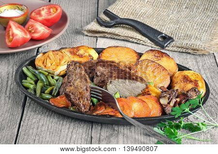Fried beef liver with vegetables, pan-fried halves of potatoes, onions, whole mushrooms, carrots and green beans on the old boards.