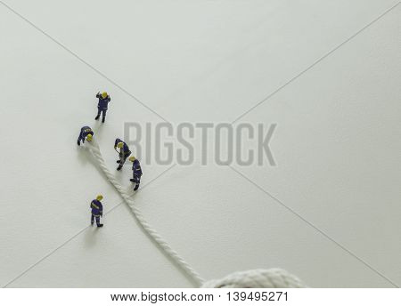 mini team of workers cut the white rope on isolate background and leave space for fill text wording - can use to display or montage on products or conceptual