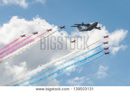 FARNBOROUGH, UK - JULY 17: Red Arrows formation flying team and an Airbus A400 transporter in the skies over Farnborough, UK on July 17, 2016