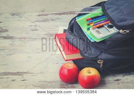 School backpack with supplies and apples on white desktop, retro toned