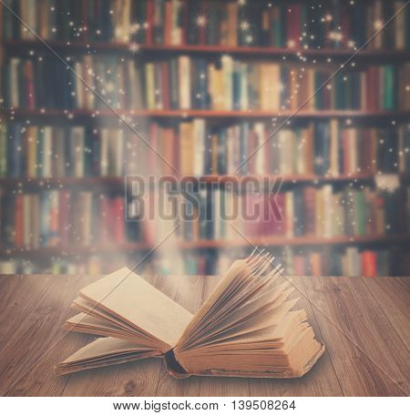 Open book on wooden book shelf with magic light, retro toned