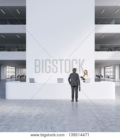 Reception in modern office. Man and woman in suits standing in front of big white table with computers. Chairs and other rooms in background. Concept of business meeting. 3d rendering. Mock up